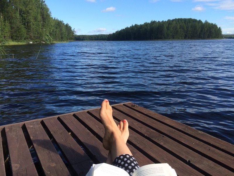 Mit einem Buch auf dem Steg im Ferienhaus am See